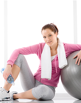 A photo of a woman with a bottle of water after exercise