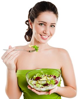 A woman eating a bowl of salad