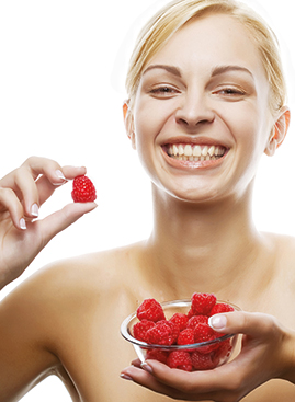 A photo of a woman with a bowl of antioxidant-rich berries